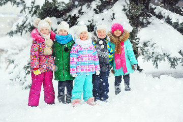 a group of small preschool children in colorful winter warm clothes are smiling against the background of snow and Christmas trees. Winter vacation.