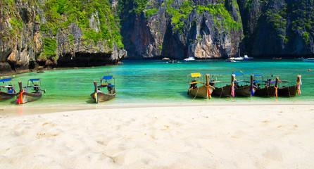 Maya Bay beach at Ko Phi Phi Leh Island with traditional longtail taxi boats .  Thailand tourist attraction, Krabi Province, Andaman Sea