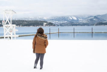 A woman stands with her back to the camera as she views the swim area and lake at Honeysuckle Beach in Hayden Lake, Idaho, USA during snowy winter