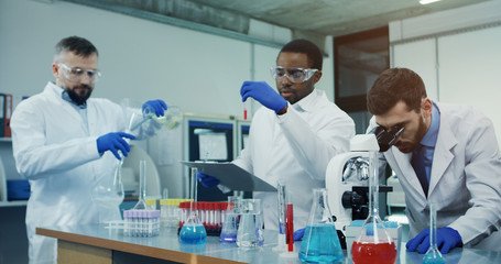 Portrait shot of the Caucasian man scientist looking in the microscope while investigating something in the laboratory, while his male mixed-races co-workers talking on the background.