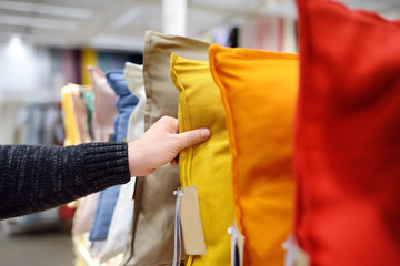 Man choices pillow in shop. Variety of colour pillows on shopping stand in supermarket