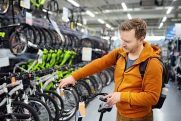 Middle age man choosing bicycle in sport store.