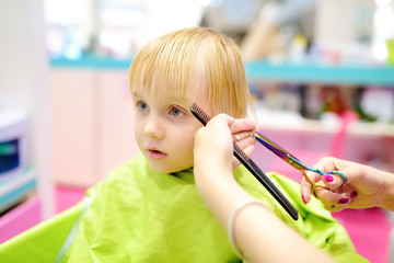 Preschooler boy getting haircut. Children hairdresser with professional tools - comb and scissors.