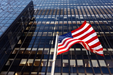 Waving American flag on the background of skyscraper in New York, usa.