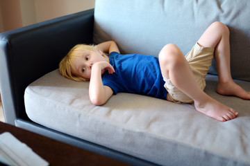 Little boy laying on couch and watching cartoons by tablet pc. Kids and gadgets. Addiction.