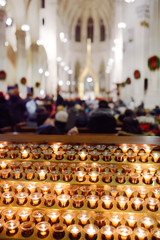 Close-up photo of church candles in transparent chandeliers in Church during catholic religious service.