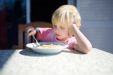 Little boy sitting the table and doesn't want to eat soup. Healthy food.