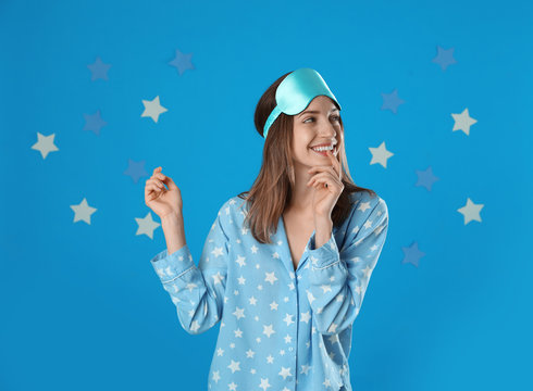 Beautiful woman wearing pajamas and sleep mask on light blue background. Bedtime