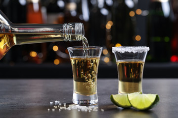 Pouring Mexican Tequila from bottle into shot glass on bar counter