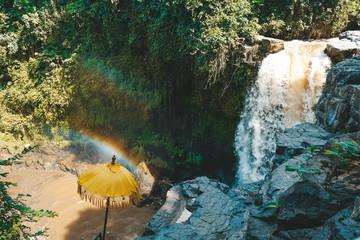 Beautiful double rainbow over bright yellow sun umbrella and cascade