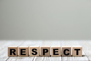 Respect word written on wood block on wooden background