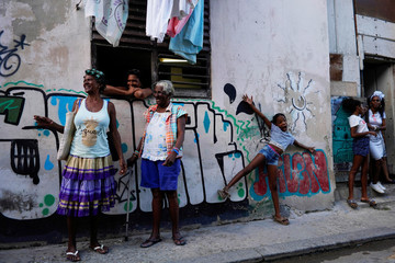 Neighbors chat as they watch Cuban and New Orleans musicians after a parade in downtown Havana