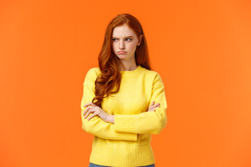 Offended angry and tensed woman with curly red hair, freckles, having bad mood, cross arms chest,...