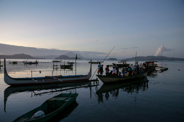 Dozens of residents ride a boat going to their homes near the errupting Taal Volcano to rescue the animals they left behind, in Talisay,