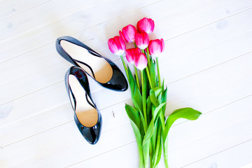 Pink tulips & black high heel shoes on white background