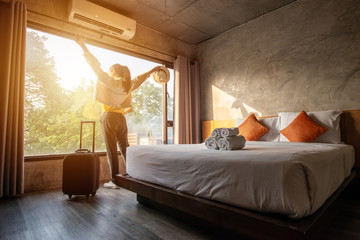 Fototapeta Tourist woman raised her hands with her luggage in hotel bedroom. obraz