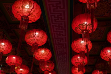Many illuminated red Chinese lanterns with some Chinese characters on it in temple - Used across countries in Asia for celebrating Chinese New Year tradition