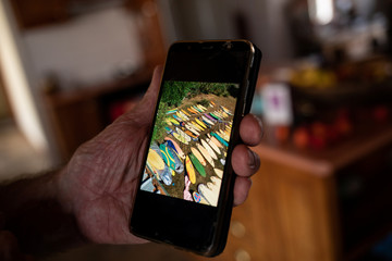Australian surfer David Ford shows a photo on his phone of a part of his vintage surfboard collection that was destroyed in the recent bushfires in Lake Conjola