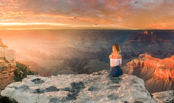 Young woman sitting on the edge of rim and enjoying the view of Grand Canyon