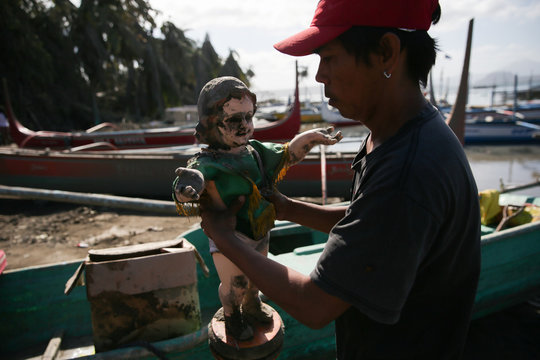 A man holds a statue of baby Jesus covered in volcanic ash, salvaged from their home near the erupting Taal Volcano
