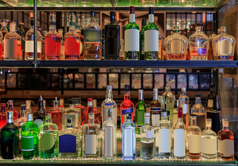 Selection of alcohol bottles on shelves on display at a bar, logos and labels removed. New York United States of America