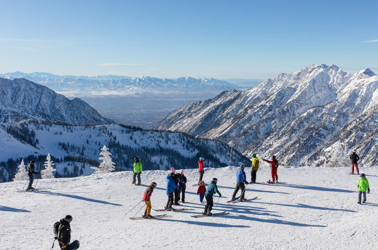 Skiers and snowboarders on top of Hidden Peak ready to ski down at Snowbird Ski Resort in Little Cottonwood Canyon in the Wasatch Range near Salt Lake City, Utah, USA.
