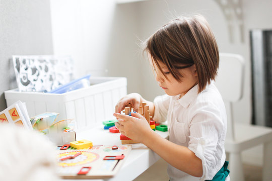 girl child plays with wooden educational toy