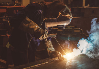 Tuinposter Muziek Industrial Worker labourer at the factory welding steel structure