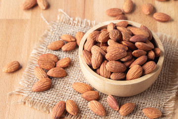 Almond seeds in a bowl wood on the sackcloth on table wooden background
