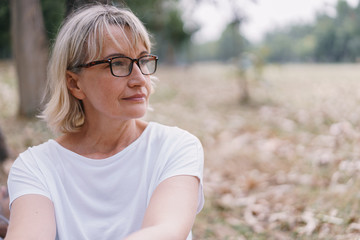 Elderly women caucasian  wear glasses while sitting  think at the public park in the autumn