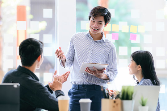 Business people discussing, talking and smiling during conference in modern office.