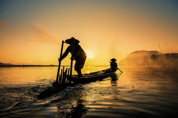 Asian Fishermen on boat fishing at lake, Thailand countryside Wall mural