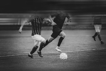 Two men play football. Black and white image. To enhance the effect of the movie, motion blur was added. Copy paste. (Faces blurred in the dark)