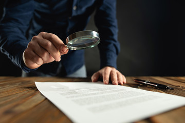 Businessman Reading Contract Using Magnifying Glass Before Signing