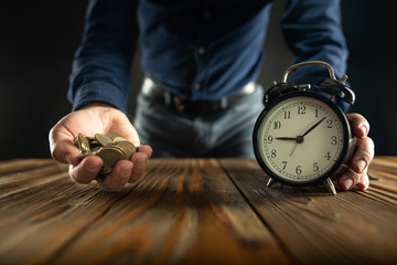Time is Money Concept with Businessman Holding Alarm Clock and Handful Coins