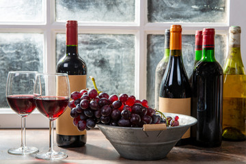 Spoed Foto op Canvas Wijn two wineglasses, red and white grapes with bottles of red wine