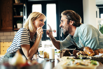 Fototapeta Beautiful young couple is smiling while cooking together in kitchen at home