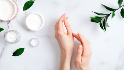 Wall Murals Spa Cosmetic cream on female hands, jars with milk swirl cream and green leaves on white marble table. Flat lay, top view. Woman applying organic moisturizing hand cream. Hand skin care concept