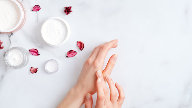 Hand skin care concept. Top view female hands applying organic moisturizing hand cream, jars with cosmetic cream and pink petal on marble table. Natural organic beauty products