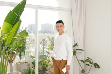 asian young man smiling in living room look at camera with hold a smartphone