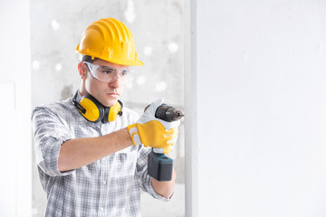Builder drilling a hole in a new wall