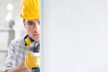 Young male construction worker drilling the wall