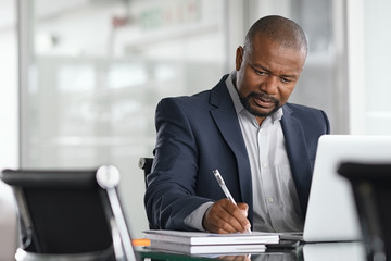 Mature businessman writing on documents