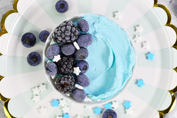 Healthy yogurt and fruit smoothie cream bowl with natural blue spirulina powder topped with blackberry and blueberry fruits