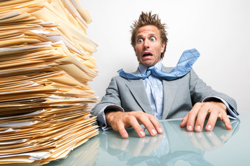 Stressed businessman sitting at his desk looking at a large pile of unfinished paperwork