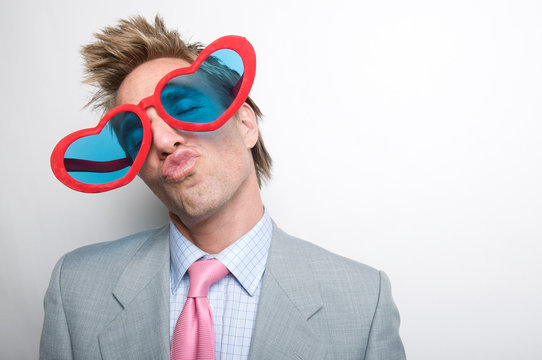 Man wearing suit with pink tie giving a big smooch to the camera behind a pair of crazy oversized heart-shaped sunglasses