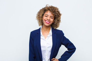 young woman african american smiling happily with a hand on hip and confident, positive, proud and friendly attitude against flat wall
