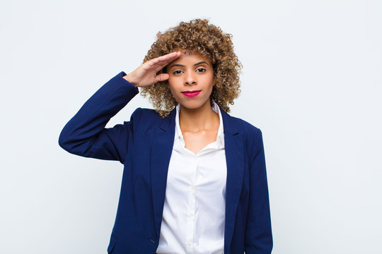 young woman african american greeting the camera with a military salute in an act of honor and patriotism, showing respect against flat wall