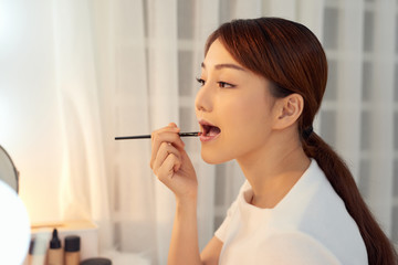 Portrait of young Asian woman applying lipstick with brush on lips
