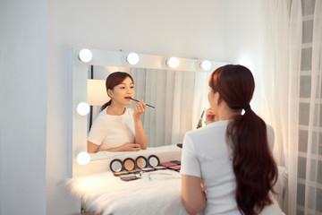 Beautiful Asian girl applying lipstick in front of mirror. Make up concept